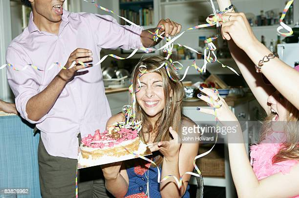 Friends throwing streamers over woman holding cake
