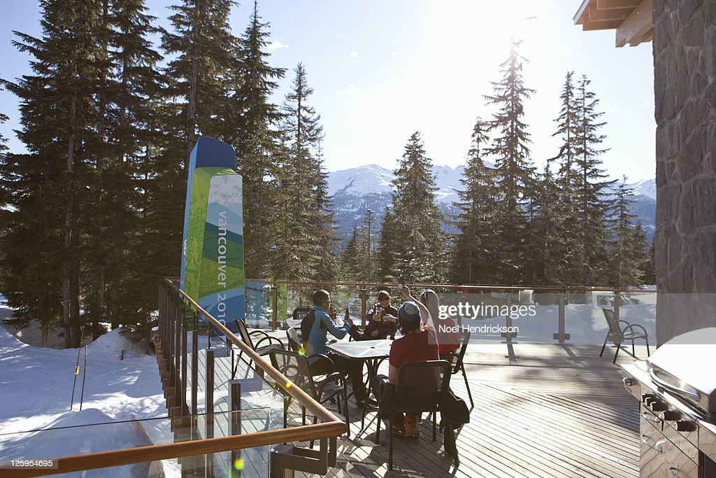 Friends toast beers on ski lodge patio : Stock Photo