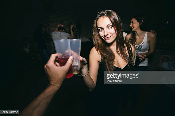 Friends toasting and drinking in nightclub