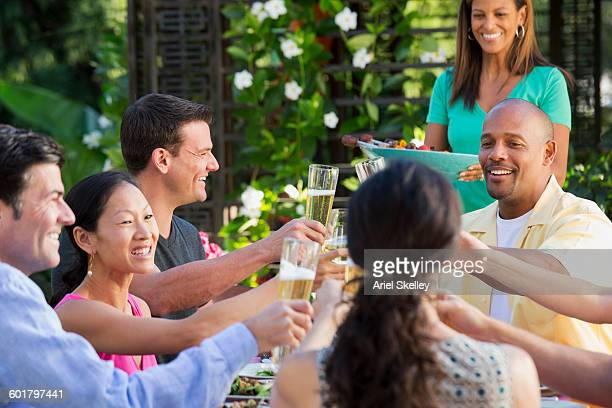 Friends toasting at table outdoors