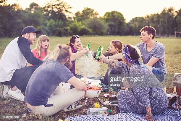 Friends toasting beers and having fun outdoors