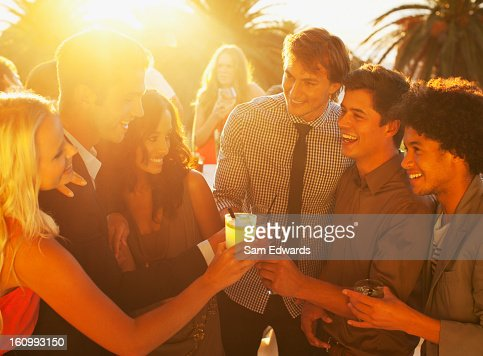 Friends toasting cocktails on sunny balcony : Stock Photo