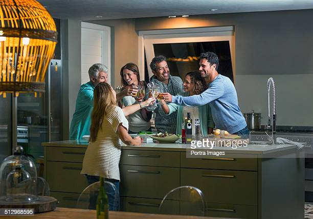 Friends toasting drink glasses over kitchen island