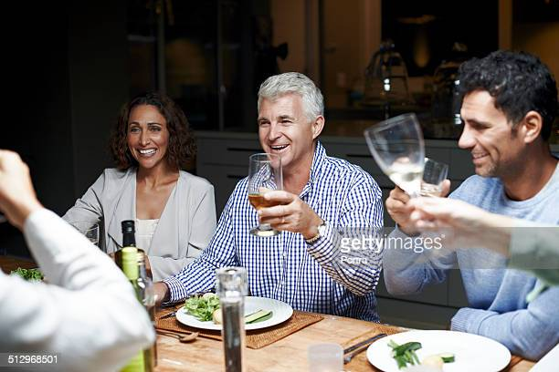 Friends toasting drinks at table