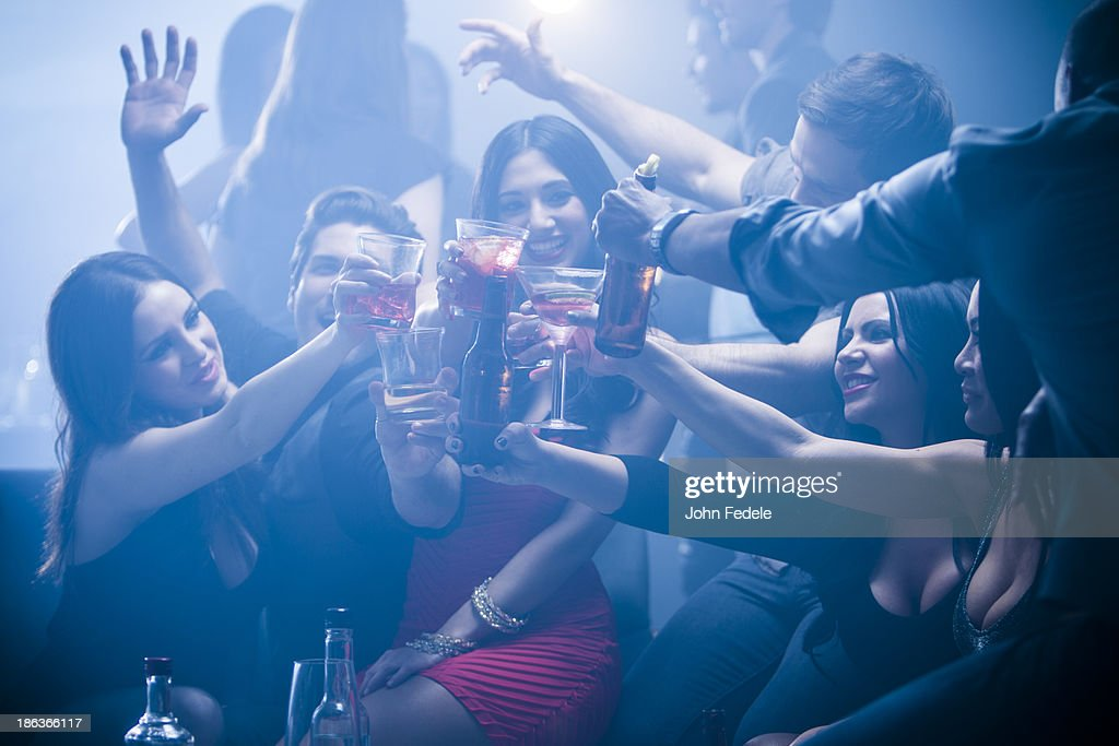 Friends toasting each other in nightclub : Stock Photo
