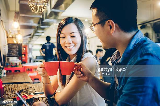 Friends toasting each other with coffee in cafe