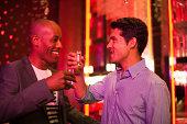 Friends toasting glasses in nightclub