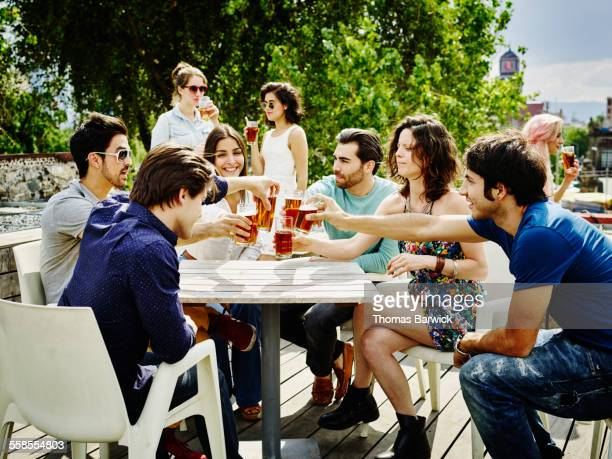 Friends toasting glasses together at party on deck