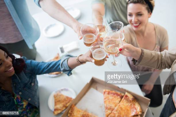 Friends toasting over box of pizza