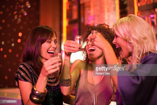 Friends toasting shot glasses in nightclub