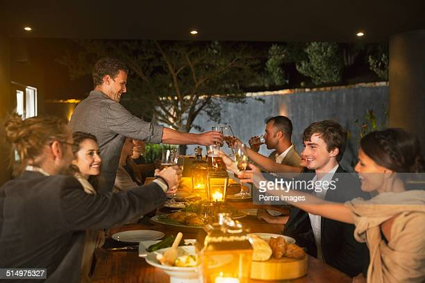 Friends toasting wineglasses at dinner table
