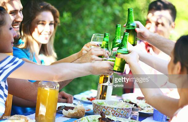 Brindis de amigos con una cerveza y vino.