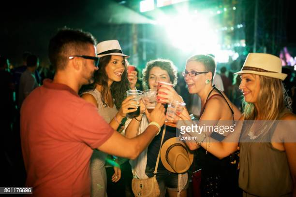 Friends toasting with beer at music festival