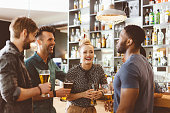 Excited multi ethnic group of friends - caucasian and afro american - gathering in the pub, talking, drinking beer.