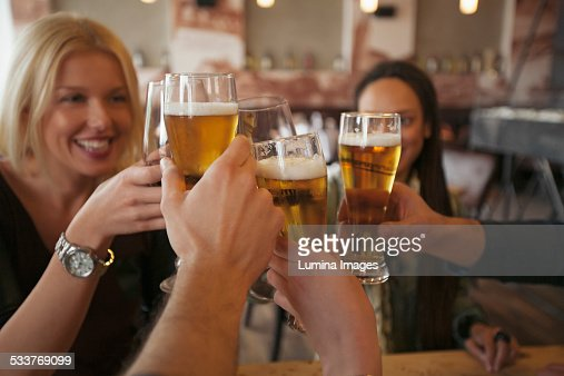 Friends toasting with beer in cafe