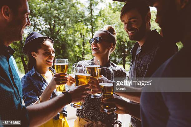 Friends toasting with beer outdoors