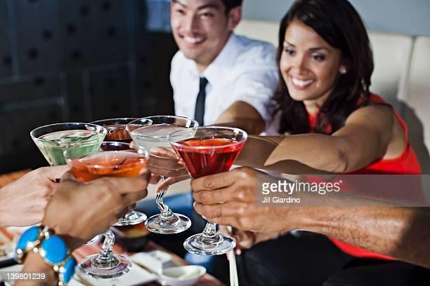 Amis portant un toast avec des cocktails dans un night-club