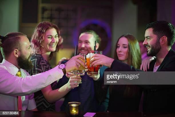 Brindis de amigos con bebida en el bar