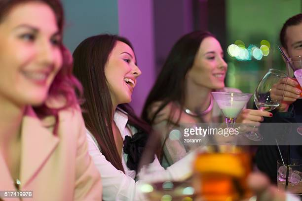 Friends toasting with drinks in nightclub