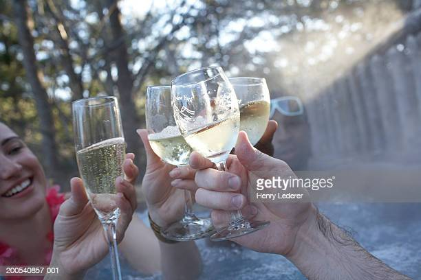 Friends toasting with glasses of beer in hot tub, close-up
