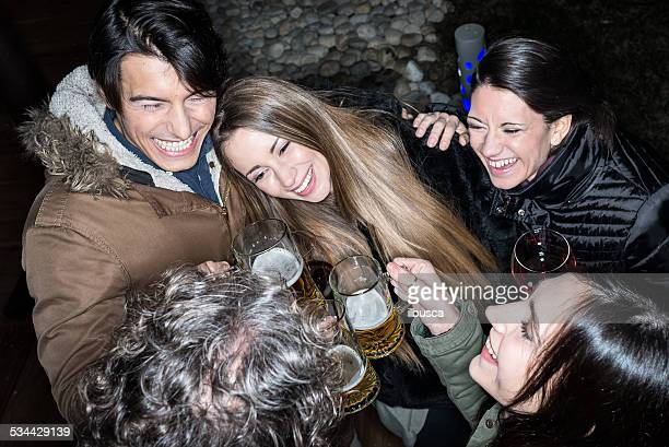 Friends toasting with wine and beer outside pub at night