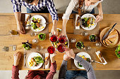 Top view of group of friends raising a toast post lunch. High angle view of happy men and women celebrating at home with red wine. Close up shot of friends toasting glasses of red wine in a party.
