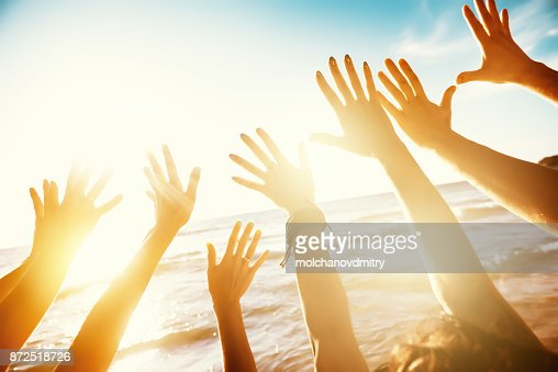 Friends travel concept with hands and sunset sea : Foto stock