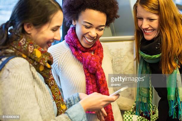 Freunde, die auf Zug mit Mobiltelefon