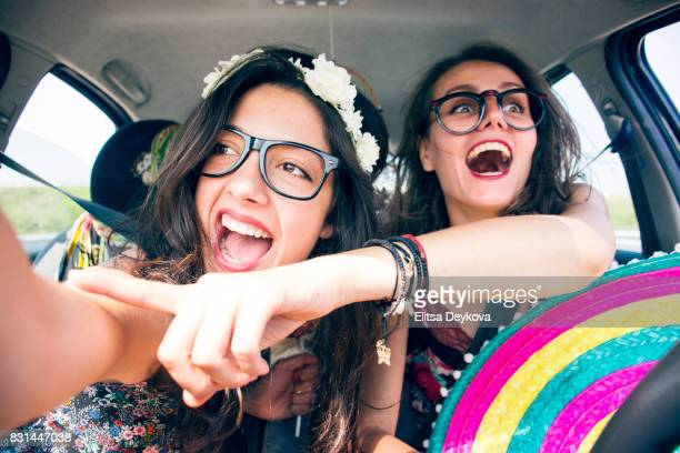 Friends travelling in a car and pointing through the window
