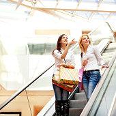 Friends, two women taking escalator in shopping mall