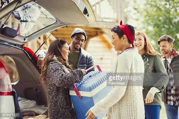 Friends unloading backpack at back of car