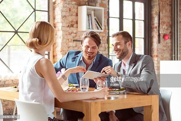 Amis à l'aide d'une tablette numérique dans le déjeuner au restaurant