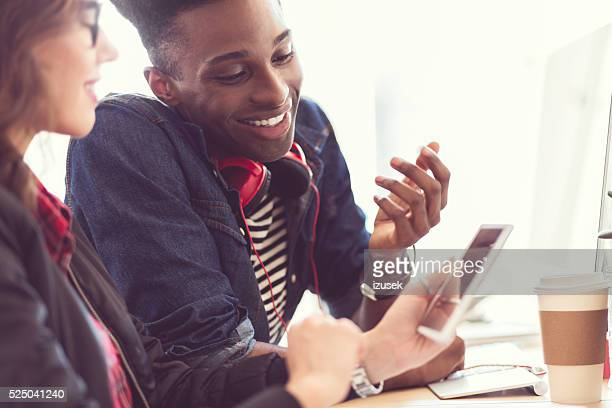 Amigos usando um tablet digital, foco na homem afro-americano