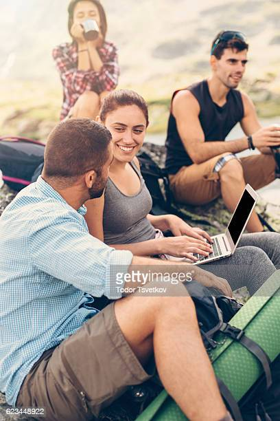 Friends using a laptop in the mountain