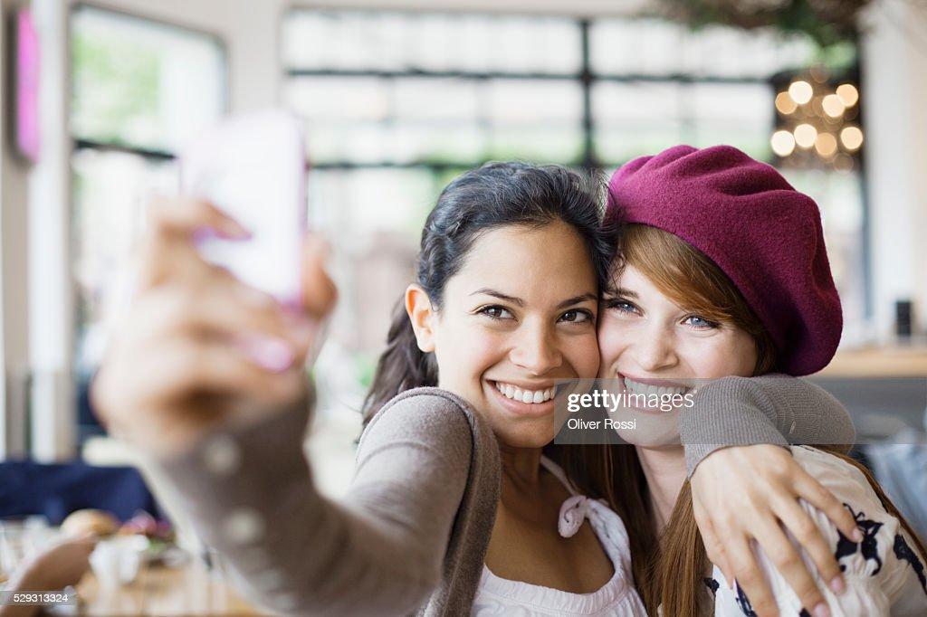 Friends using camera phone in cafe : Foto de stock