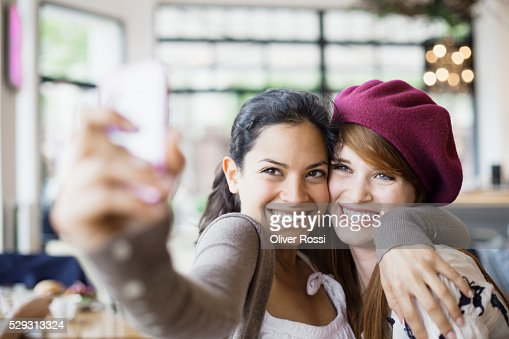 Friends using camera phone in cafe : Stock Photo