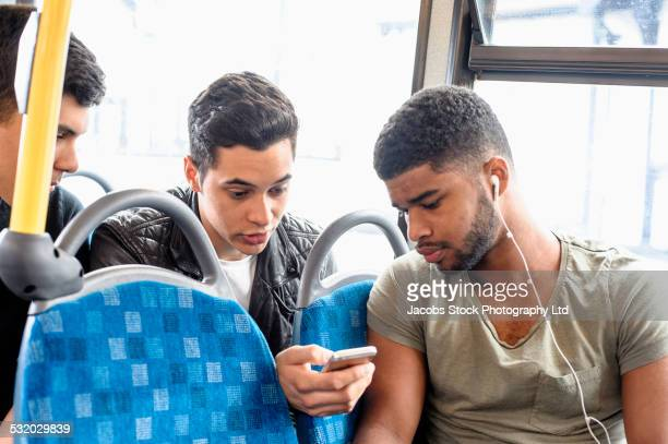 Friends using cell phone on bus