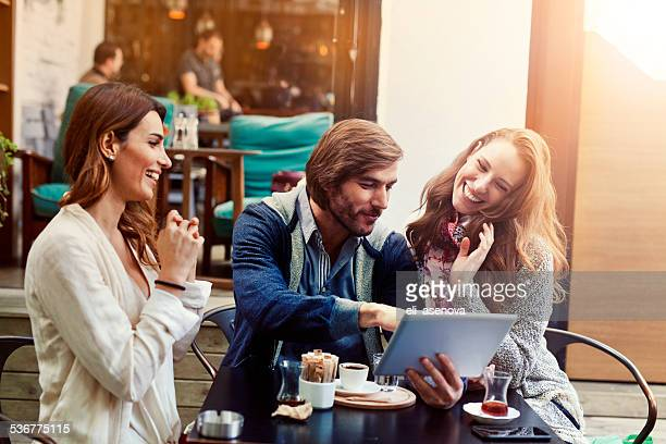 Friends using digital tablet in a cafe, Istanbul.
