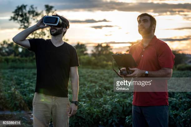 Friends Using Drone and Virtual Reality Headset at Sunset