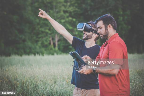 Friends Using Drone and Virtual Reality Headset Outdoor