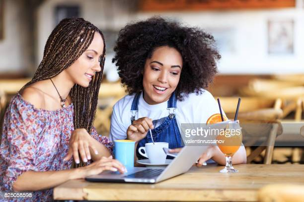Amigos utilizando la computadora portátil en cafetería