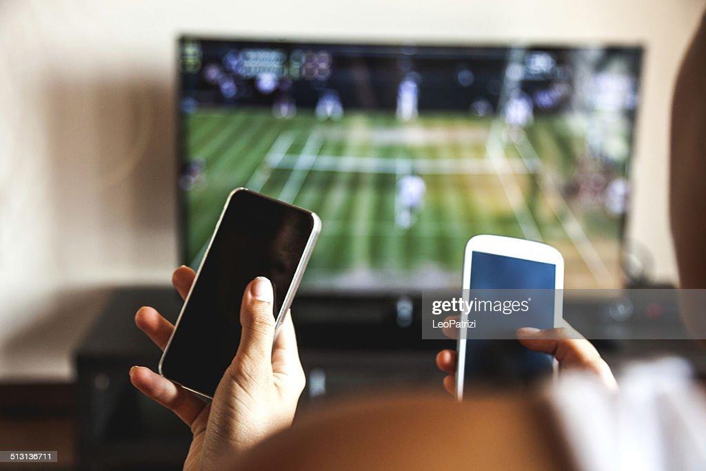 Amis à l'aide d'un téléphone mobile pendant un match de tennis : Photo