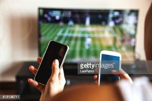 Amici utilizzando il telefono cellulare durante una partita di tennis