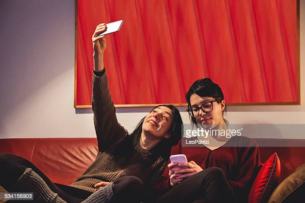 Friends using mobile phone while whatching TV