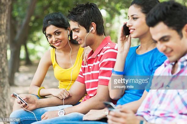 Friends using mobile phones and mp3 player in a park, Lodi Gardens, New Delhi, Delhi, India