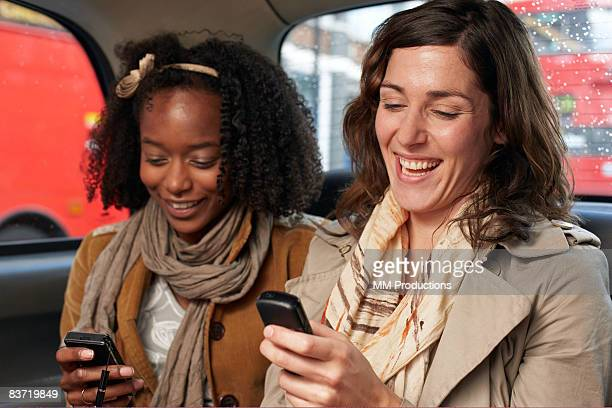 Friends using mobiles in taxi