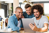 Young guys in casual clothes smiling and discussing ideas using tablet at cafe. Group of friends looking at digital tablet. Happy multiethnic young men watching video on digital tablet in a wifi cafe.
