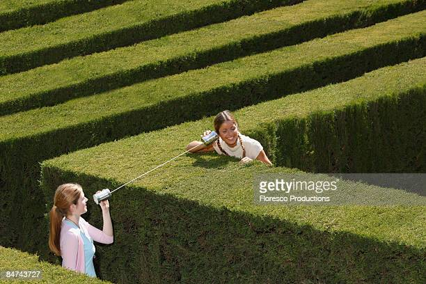 Friends using tin can telephone in hedge maze