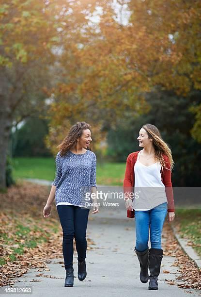 Friends walking along path in urban park.