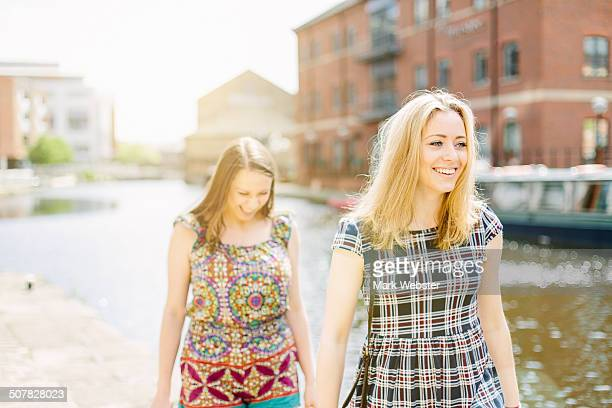 Friends walking by canal, Leeds, England